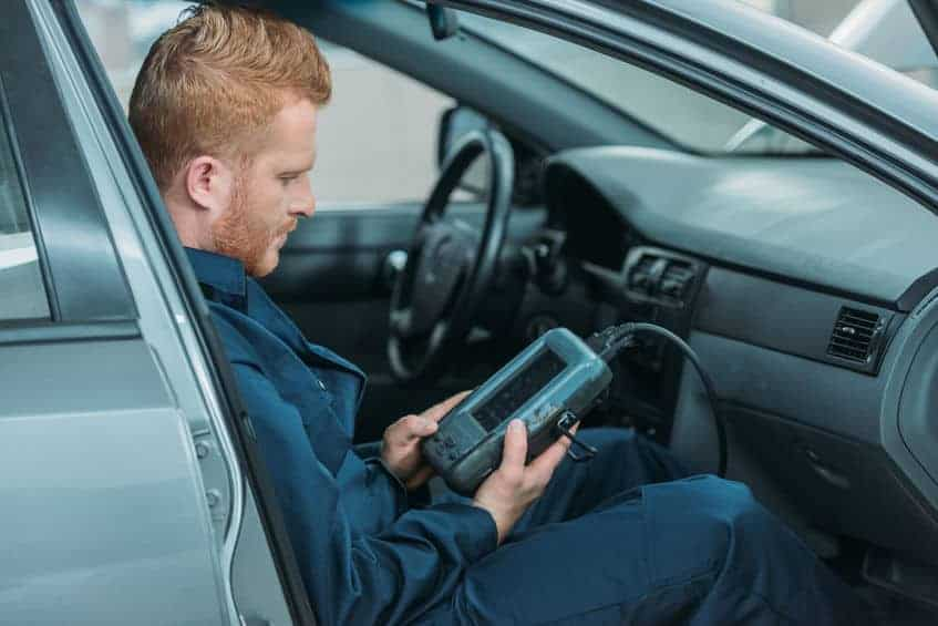 Mechanic using an OBD2 scanner in the vehicle