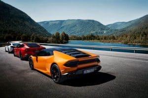 Three exotic cars beside the lake on the side of the road - Lamborghini Ferrari McLaren