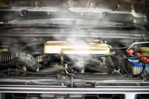 Car overheating radiator blowing out hot smoke