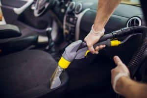 Cleaning the seat of a car with a vacuum cleaner
