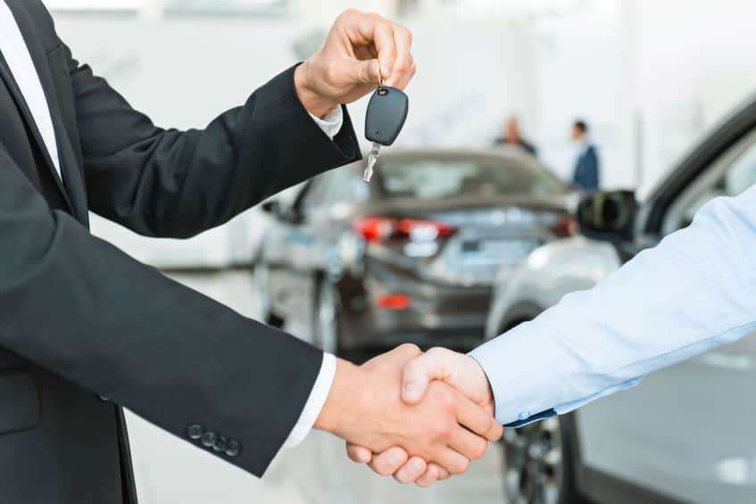 Car salesman handing over the keys to the recently purchased vehicle