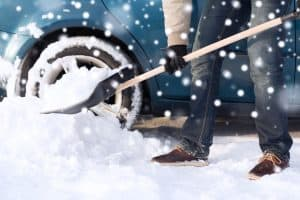 Shoveling snow around the car
