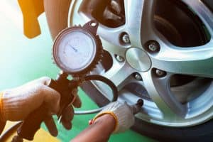 Inflating the tire of a car and checking the tire pressure gauge