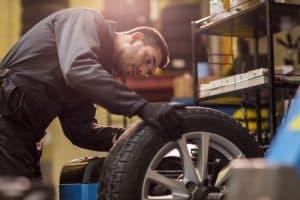 Car shop mechanic balancing the tire wheel on the machine