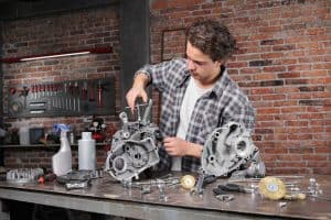 Man working with the socket wrench, repair and cleaning engine parts on the workbench in home garage workshop DIY
