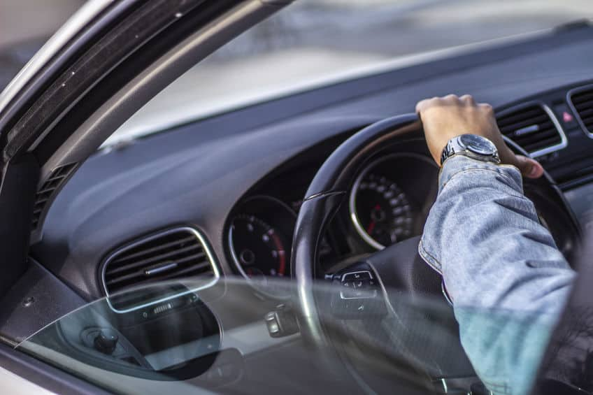 An over-the-shoulder shot of a Young Man holding the car steering wheel