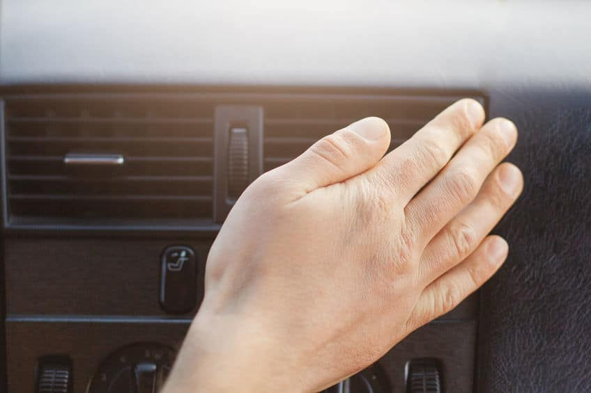 Man`s hand on car heater or conditioner, regulates temperature in automobile while drives. Car`s accessories or panel. Conditioning concept.