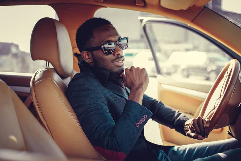 Blackman in sunglasses driving a car.