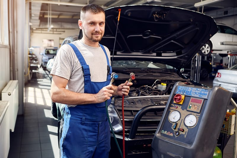 AC Car Mechanic Inspecting Air Conditioning in Vehicle