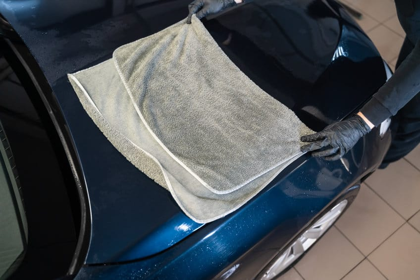 Car wash worker wipes the car after washing with microfiber towel. Professional car wash