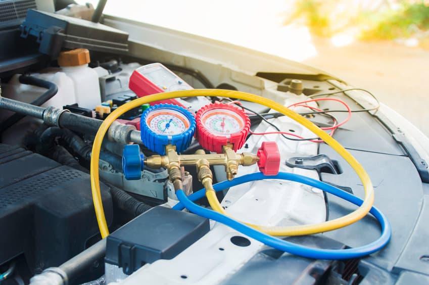 Auto mechanic uses a pressure gauge on the air compressor,liquid