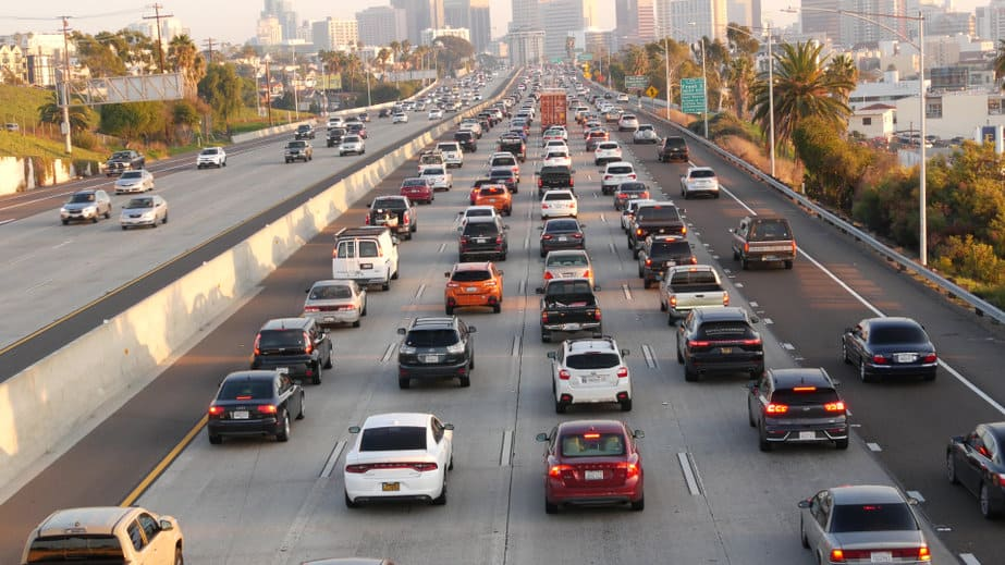 SAN DIEGO, CALIFORNIA USA - 15 JAN 2020: Busy intercity freeway, traffic jam on highway during rush hour. Urban skyline and highrise skyscrapers. Transportation concept and transport in metropolis