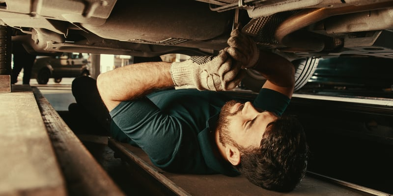 Mechanic under the car wrenching