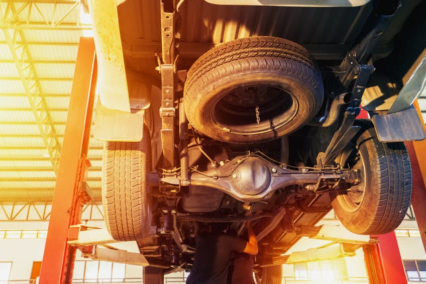 Mechanic inspect car suspension system and chassis under the pickup truck
