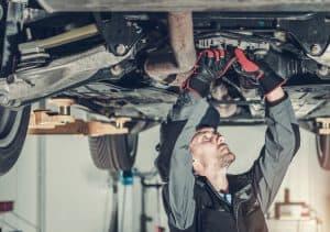 Mechanic fixing a car hoisted up on a hydraulic lift