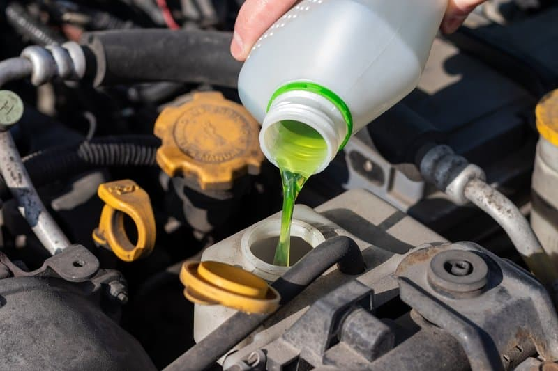 Pouring anti-freeze engine coolant into the reservoir