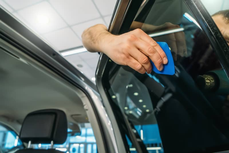 Window tint - being installed by a professional detailer