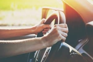 Car driving on the road with hands on the steering wheel