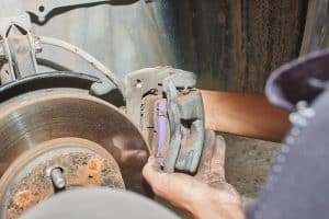 Car mechanic removing the brake caliper with brake pads from the rotor