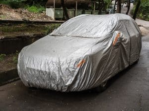 Car parked on the side of the road with a car cover on it