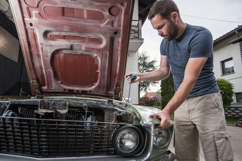 Young man wrenching on an old vintage car